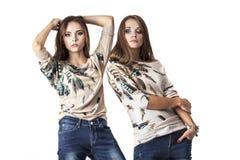 Les femmes sont deux modèles dans des vêtements à la mode dans des jeans dans le goujon Photo libre de droits