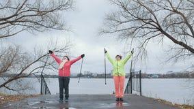 Les femmes supérieures en parc d'automne ont la formation - réchauffez avant la marche nordique Photos stock