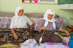 Les femmes supérieures tournent la laine pour la production de tapis dans Karacahisar, Turquie Photographie stock libre de droits