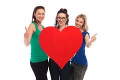 Les femmes tenant un grand coeur et font le signe correct Photo libre de droits
