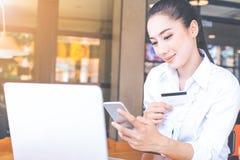 Les femmes tiennent des cartes de crédit et des téléphones portables d'utilisation pour faire des achats Photographie stock