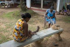 Les femmes tissent la corde des cosses de noix de coco Photos stock
