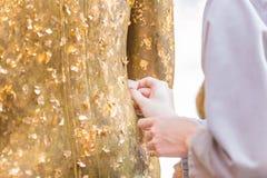 Les femmes utilisent la feuille d'or sur le Bouddha photographie stock libre de droits
