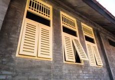 Les fenêtres de vintage sur le mur de briques rugueux Photos stock