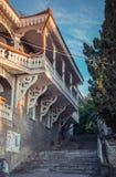 Les fenêtres et le balcon extrêmement fleuris, bâtiment de vintage, une vue du beau bois ont peint les détails blancs Photos stock