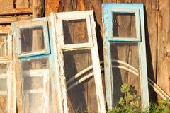 Les fenêtres sont dans différentes couleurs dans le rétro style Support près du mur en bois Image stock
