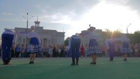 Les festivités folkloriques, les jeunes garçons et les filles dans des costumes nationaux dansent le hopak dans la place de ville banque de vidéos
