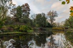 Les feuilles d'automne colorent un jardin avec le lac et le pont Photo libre de droits