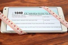 Les feuilles d'impôt des USA 1040 s'ouvrent dans des smartphones Photographie stock