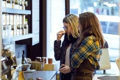 Les feuilles de thé sentantes de belle jeune femme se sont vendues en poids dans la boutique organique photographie stock