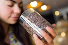 Les feuilles de thé sentantes de belle jeune femme se sont vendues en poids dans la boutique organique Photos stock