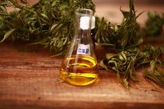 Les feuilles de vert de médecine des cannabis médicinaux avec l'extrait huilent sur une table en bois image stock