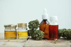 Les feuilles de vert de médecine parallèle des cannabis médicinaux avec l'extrait huilent sur une table en bois images stock