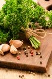 Les feuilles du persil et de l'épice sur une cuisine embarquent Photo libre de droits