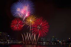Les feux d'artifice colorés au-dessus du ciel nocturne, les feux d'artifice rouges raye Images stock