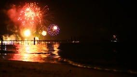 Les feux d'artifice d'or lumineux éclatent dans le ciel nocturne au-dessus de la surface de la mer banque de vidéos