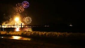 Les feux d'artifice d'or lumineux éclatent dans le ciel nocturne au-dessus de la surface de la mer clips vidéos