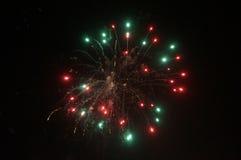 Les feux d'artifice rouges et verts ont éclaté dans l'air Photographie stock libre de droits