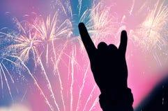 Les feux d'artifice sur le ciel et la main faisant la roche signent Images stock