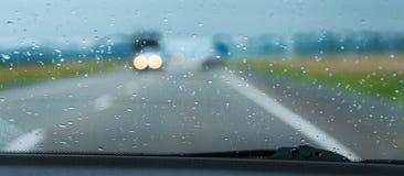 Les feux de signalisation brouillés vus par la pluie chute Photographie stock