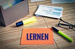 Les fiches avec des thèmes légaux avec les verres, le stylo et le bambou et le mot allemand lernen en anglais apprennent images libres de droits