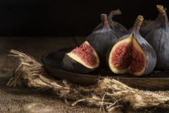 Les figues fraîches dans l'éclairage naturel déprimé ont placé avec le rétro styl de vintage Photo libre de droits