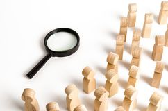 Les figures en bois des personnes regardent la loupe Recherche des réponses aux questions, recherches de maison ou travail Résolu image libre de droits