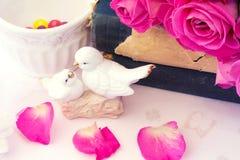 Les figurines épousant des colombes dans le bouquet de Valentine d'amour des roses roses sur le fond floral de vieux livres est S Photographie stock