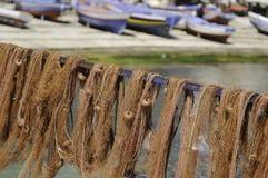 Les filets de pêche rouges pittoresques ont traîné pour sécher et les bateaux colorés Photo libre de droits