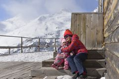 les Fille-soeurs s'asseyent dans une étreinte sur des étapes de la maison en bois en montagnes image stock