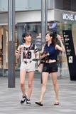 Les filles à la mode marchent dans la zone d'atelier de village, Pékin, Chine Photos stock