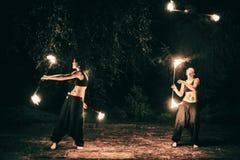 Les filles actives effectue des tours pour l'exposition du feu la nuit Images stock