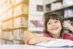 Les filles asiatiques sont des livres de lecture et écouter la musique Images libres de droits