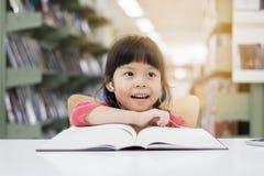 Les filles asiatiques sont des livres de lecture et écouter la musique Photographie stock