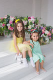 Les filles assez petites dans un jaune et des robes de turquoise reposent près de l'des fleurs dans un studio Photographie stock libre de droits