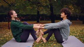 Les filles attirantes font des exercices de yoga dans les paires tenant des mains et mettant des pieds soulevant ensemble des jam clips vidéos