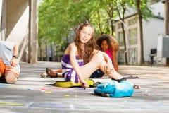Les filles avec des amis dessine dans la craie dehors Image libre de droits