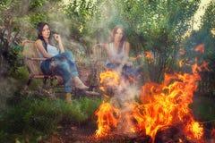 Les filles avec des verres de vin rouge s'approchent du feu Images stock