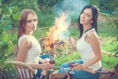 Les filles avec des verres de vin rouge s'approchent du feu Image stock
