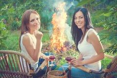 Les filles avec des verres de vin rouge s'approchent du feu Photos libres de droits