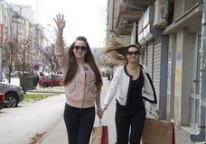 Les filles avec les sacs du magasin courent pour un taxi photo libre de droits
