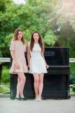 Les filles caucasiennes apprécient le week-end d'été dans piano proche extérieur de parc le grand Jeunes amis de touristes en vac Photo stock