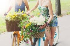 Les filles chics de boho heureux montent ensemble sur des bicyclettes en parc Photo stock
