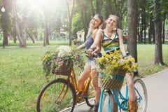 Les filles chics de boho heureux montent ensemble sur des bicyclettes en parc Photos libres de droits