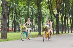Les filles chics de boho heureux montent ensemble sur des bicyclettes en parc Image libre de droits