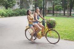 Les filles chics de boho heureux montent ensemble sur des bicyclettes en parc Image stock