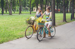 Les filles chics de boho heureux montent ensemble sur des bicyclettes en parc Photographie stock libre de droits