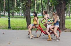 Les filles chics de boho heureux montent ensemble sur des bicyclettes en parc Images stock