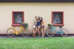 Les filles chics de boho heureux posent avec des bicyclettes près de la façade de maison Photos stock