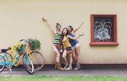 Les filles chics de boho heureux posent avec des bicyclettes près de la façade de maison photographie stock libre de droits
